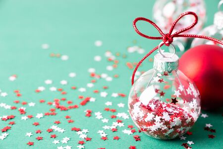 Close up of transparent Chritmas balls with star shape glitter inside on a turquoise background