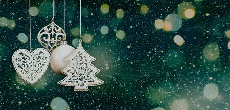 Hanging white Christmas baubles in a nordic style with blurred lights, sparks and snow on a dark greenish blue background. Copy space