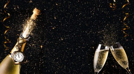 New year celebration concept with a bottle of champagne with a clock exloding fireworks, sparks and confetti and two glasses toasting on a dark background. Copy space