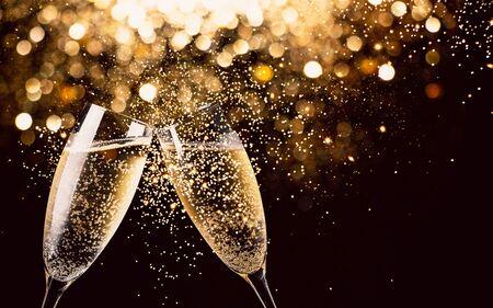 Dos copas de champán brindando en la noche con luces bokeh, purpurina y chispas en el fondo Foto de archivo