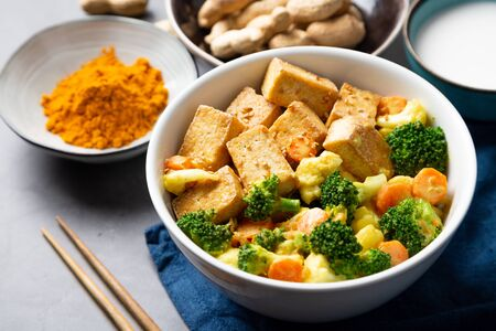 Stir fried tofu and vegetables with satay sauce in a bowl