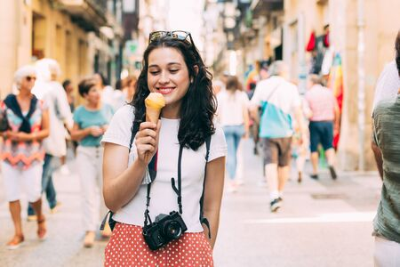 Young tourist woman enjoying and ice cream in a lively street of an  european city in summer Imagens