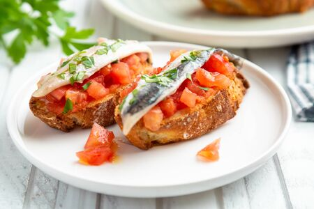 Delicious spanish tapa with marinated anchovies in vinegar, fresh tomato, olive oil and parsley on slices of toasted bread