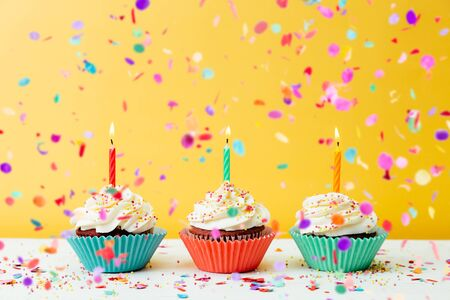Three colorful  birthday cupcakes with candles and confetti on a yellow background