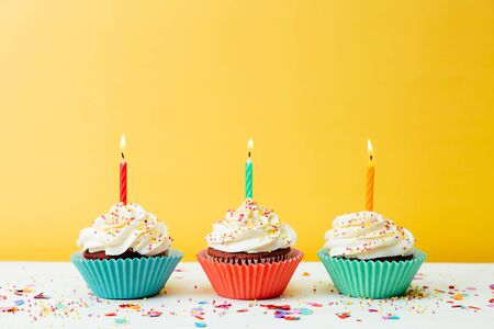 Three colorful birthday cupcakes with candles and confetti on a yellow background Stockfoto