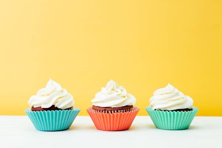 Three colorful red velvet cupcakes on a yellow background