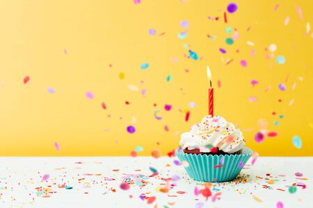 A colorful  birthday cupcake with one candle and confetti on a yellow background Imagens