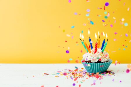 A colorful  birthday cupcake with seven candles and confetti on a yellow background