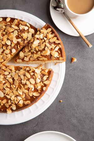 Almond and lemon cake with sliced almonds topping and a coffee cup on a concrete surface. Top view