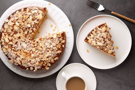 Almond and lemon cake with sliced almonds topping and a coffee cup on a concrete surface. Top view Imagens - 146466158