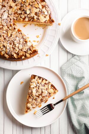 Almond and lemon cake with sliced almonds topping and a coffee cup on a white wooden table. Top view
