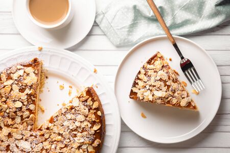 Almond and lemon cake with sliced almonds topping and a coffee cup on a white wooden table. Top view Imagens - 146466083
