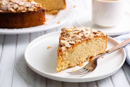 Almond and lemon cake with sliced almonds topping and a coffee cup on a white wooden table