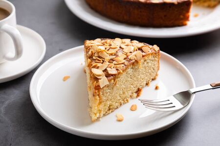 Almond and lemon cake with sliced almonds topping and a coffee cup on a concrete surface Imagens