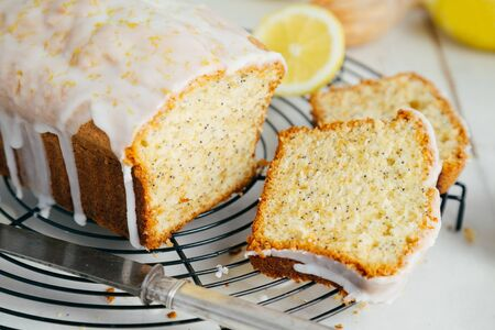 Glazed lemon pound cake loaf with poppy seed and lemon zest on a cooling rack Imagens