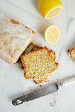 Glazed lemon pound cake loaf with poppy seed and lemon zest on a white rustic wooden table. Top view