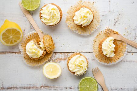 Lemon and poppy seed cupcakes with cheese cream frosting and lemon and lime zest on a rustic white wooden table. Top view