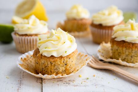 Lemon and poppy seed cupcakes with cheese cream frosting and lemon and lime zest on a rustic white wooden table