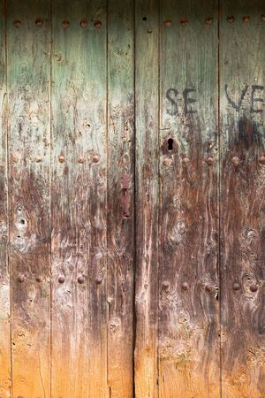 Old rustic wooden door with different layers of cracked paint in green, brown and orange colors Imagens