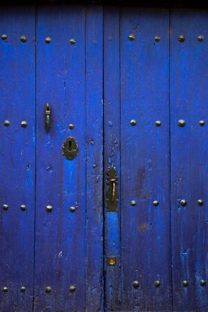 Old rustic wooden door with different layers of cracked dark blue paint