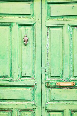 Old rustic wooden door with different layers of cracked bright green paint