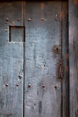 Old rustic wooden door with different layers of cracked paint in gray color Imagens