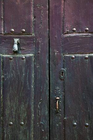 Old rustic wooden door with different layers of cracked paint in dark purple and green colors Imagens