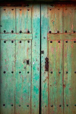 Old rustic wooden door with different layers of cracked paint in green and orange colors