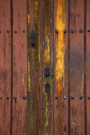 Old rustic wooden door with different layers of cracked paint in orange and yellow colors Imagens - 148480054