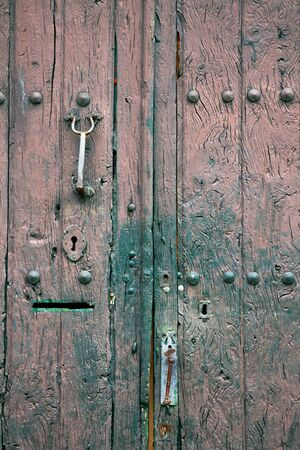 Old rustic wooden door with different layers of cracked paint in pink and green colors