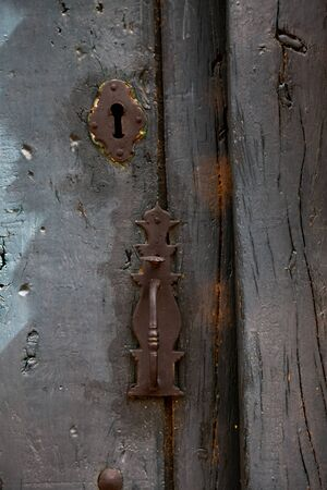 Detail of a rusty handle and lock of an old rustic wooden door with different layers of gray paint Imagens - 148479956