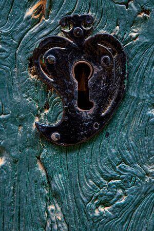 Old heart shaped door lock on a textured wooden door painted in blue Imagens - 149828655