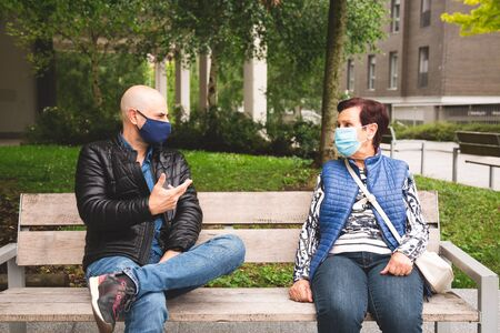 Old woman with her mature son wearing face mask sitting on a bench outdoor keeping social distance in the new normal