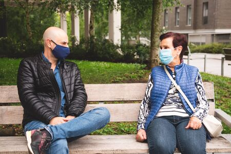 Old woman with her mature son wearing face mask sitting on a bench outdoor keeping social distance in the new normal Imagens - 150019848