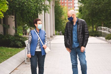 Old woman with her mature son wearing face mask walking outdoor keeping social distance in the new normal