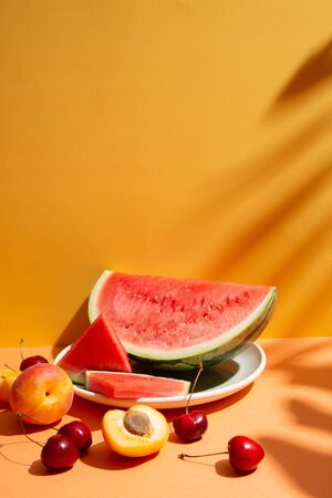 Trendy summer fruit composition with tropical leaves shadows on an orange and yellow set. Copy space Imagens - 149038755