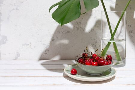 Cherries in a green bowl under monstera leaves in a glass vase on a rustic white table and wall with harsh shadows. Copy space Imagens - 149038555