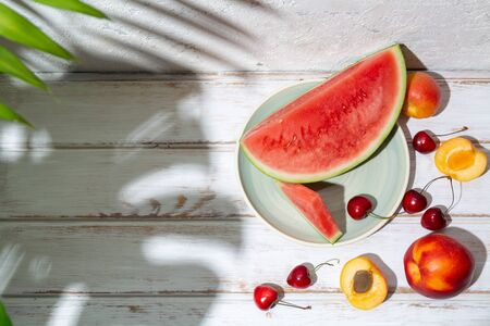 Summer fruit composition with tropical leaves shadows on a white wooden table and concrete wall. Copy space Imagens