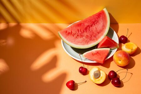 Trendy summer fruit composition with tropical leaves shadows on an orange and yellow set. Copy space Imagens - 149039606