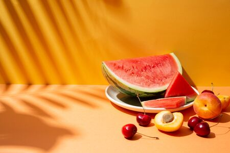 Trendy summer fruit composition with tropical leaves shadows on an orange and yellow set. Copy space