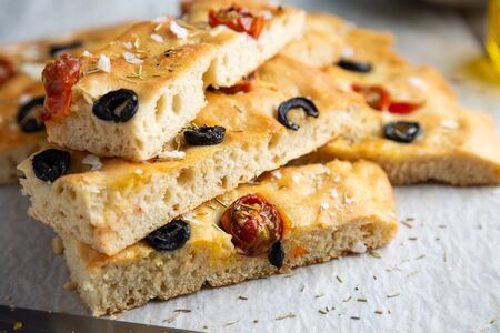 Stack of homemade focaccia with black olives, cherry tomatoes, rosemary, flake salt and olive oil on baking paper