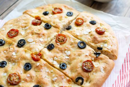 Homemade focaccia with black olives, cherry tomatoes, rosemary, flake salt and olive oil on baking paper