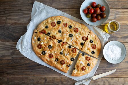 Homemade focaccia with black olives, cherry tomatoes, rosemary, flake salt and olive oil on a rustic wooden table. Top view Imagens