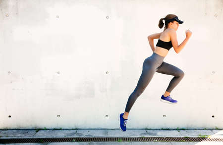 Young and healthy woman running and jumping outdoor with a white wall in the background