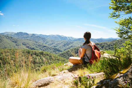Hiker girl sitting on a rock contemplating the landscape of mountains in summer Imagens