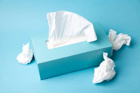 Light blue tissue box and crumpled tissues on blue background. Cold and flu concept. Minimal monochromatic composition.