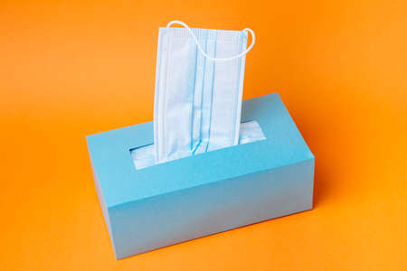 Disposable  blue face mask box on orange background. Minimal composition.