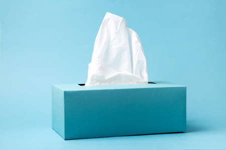 Light blue tissue box on blue background. Cold and flu concept. Minimal monochromatic composition. Imagens - 151984249
