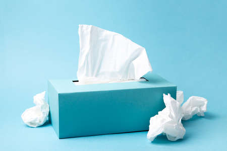 Light blue tissue box and crumpled tissues on blue background. Cold and flu concept. Minimal monochromatic composition. Imagens - 151984250
