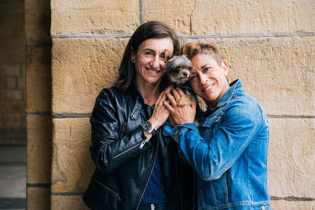 Portrait of a happy middle aged lesbian couple hugging their yorkshire terrier